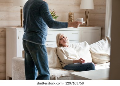 Loving aged husband care about beloved wife making her hot drink, smiling senior woman happy seeing spouse bringing tea, romantic elderly couple spending weekend in countryside together