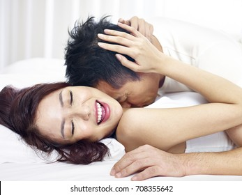 loving asian couple kissing and making love in bed.