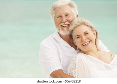 Loving attractive senior male and female Caucasian couple in white casual clothes on a tropical vacation beach