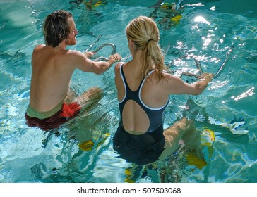 Loving beautiful couple exercising with aquatic bikes in spa center