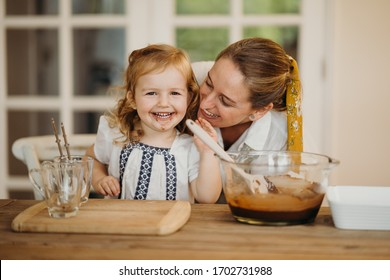 Loving beautiful mother and daughter cooking together a chocolate brownie and having fun