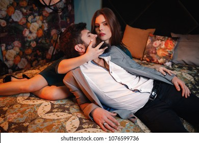 Loving beautiful pretty woman embracing stroking handsome sexy bearded man sitting on bed, young sensual sexy girl hugging lover, romantic satisfied couple relaxing in bedroom caressing each other