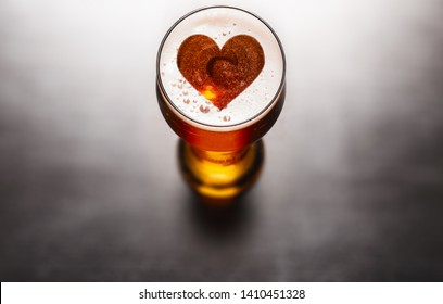 Loving beer concept. Heart symbol on beer glass foam on black table, view from above