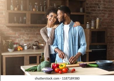 Loving black couple preparing salad in loft kitchen at home