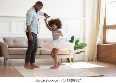 Photo of Loving black dad holding hand of child daughter dancing with his child princess wearing skirt, happy young african father and little cute daughter playing in living room enjoy time together at home