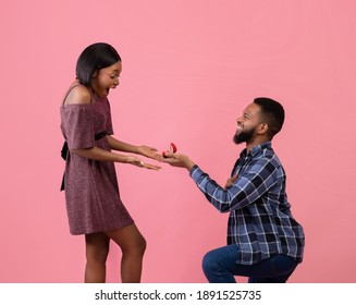 Loving black man standing on one knee and offering engagement ring to his beloved woman on pink studio background. Affectionate guy making proposal to sweetheart on Valentine's Day