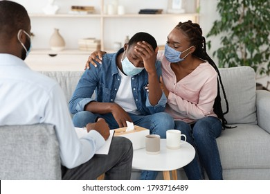 Loving Black Wife Comforting Upset Husband Having Coronavirus Panic Attacks, Sitting At Psychiatrist Office Together
