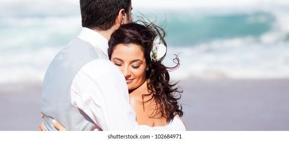 loving bride and groom hugging on beach