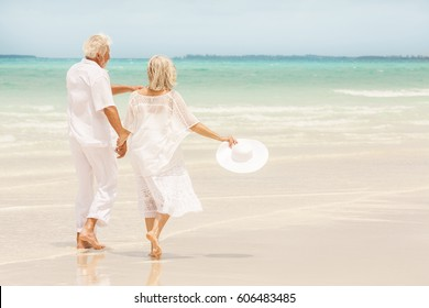 Loving Caucasian senior retired couple in white casual clothes walking together on luxury Caribbean vacation beach