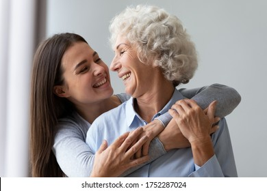 Loving cheerful grown up daughter hugs elderly mother from behind, multi generational relatives beautiful women enjoy time together laughing having fun, love care understanding concept, close up image