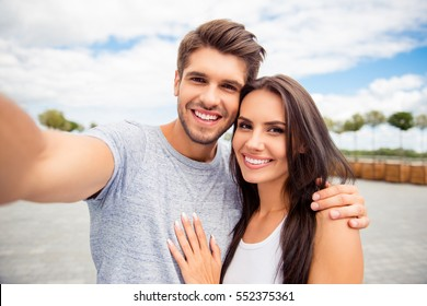 Loving cheerful happy couple taking selfie in the city