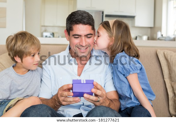 Loving children gifting father in living room