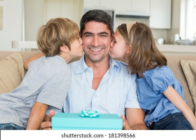 Loving children kissing on fathers cheeks at home