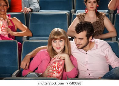 Loving couple with bag of popcorn in theater