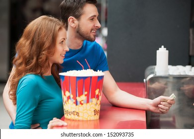 Loving couple in bar. Young loving couple buying popcorn and soda at the cinema bar