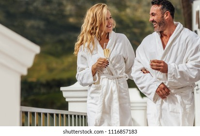 Loving couple in bathrobe walking in the balcony with glass of wine and smiling. Man and woman wearing bathrobes in their luxury villa.