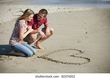 Loving couple at the beach drawing a heart in the sand