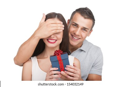 Loving couple. Beautiful young loving couple standing isolated on white while woman holding gift box