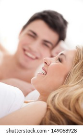 Loving couple in bed. Cheerful young loving couple lying on bed and smiling