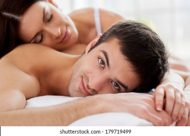 Loving couple in bed. Cheerful young loving couple lying in bed and smiling at camera