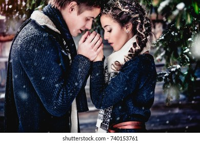 a loving couple a blond man holds the hands of his beloved brunette beautiful woman and warms them with their breath under white snow flakes against the background of wooden house and snow-covered fir