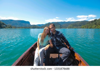 A loving couple boy and girl are sailing on a boat on a lake. The mountains, the blue surface  water, the bright blue sky create a mood of serenity and happiness. Travel Europe Switzerland