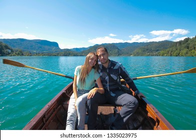 A loving couple boy and girl are sailing on a boat with oars on a lake. The mountains, the blue surface  water, the bright blue sky create a mood of serenity and happiness. Travel Europe Switzerland