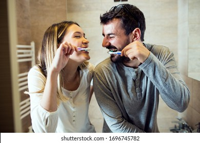 Loving couple brushes their teeth in the morning