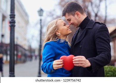 A loving couple in a coat with balloons hearts in hands.