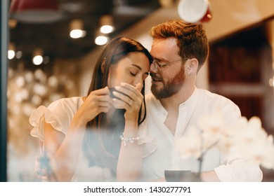 Loving couple in a coffee shop. Happy young couple is drinking coffee and smiling while sitting in a coffee shop
