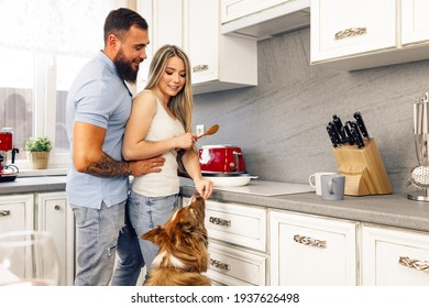 Loving couple cooking food in kitchen with their Border Collie dog