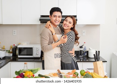 Loving couple cooking together in the kitchen at home