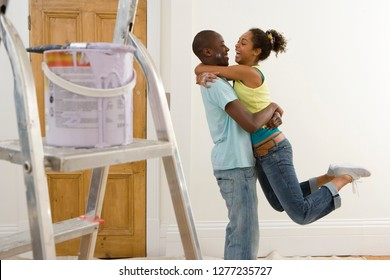 Loving couple decorating room with paint pot and ladder