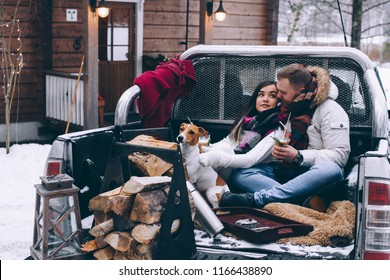 A loving couple with a dog sit in the car in the winter. Christmas holidays. lovers in the car