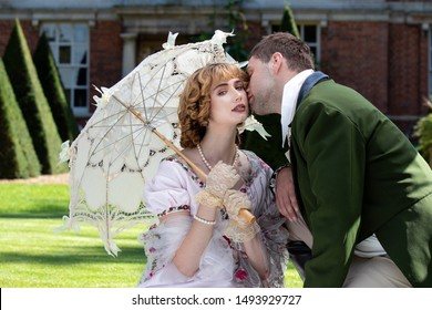 Loving couple dressed in vintage costume relax and kiss on lawn of stately home
