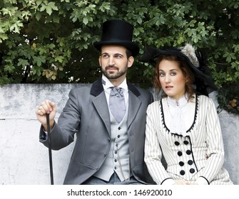 A loving couple, dressed in vintage style sitting in the park.