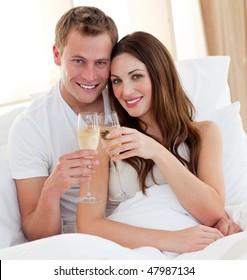 Loving couple drinking champagne lying in bed at home