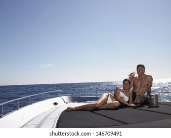 Loving couple drinking champagne while relaxing on yacht