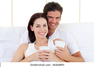 Loving couple drinking coffee lying in the bed