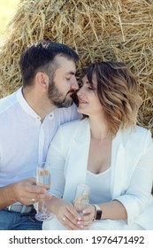Loving couple drinking vine at sunset on a wheat field near haystack. A boyfriend and a girl on a romantic date, sitting near a haystack and drinking champagne from glasses.