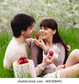Loving couple eating strawberry outdoor