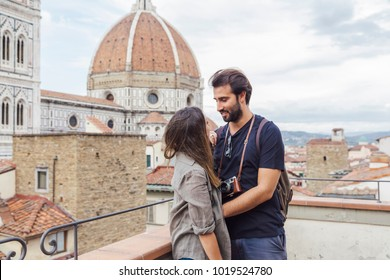 Loving couple embrace in front of the church Santa Maria del Fiore, Florence Cathedral