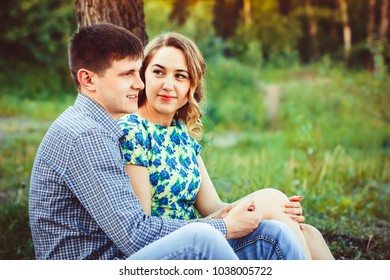 Loving couple embracing sitting in the woods.