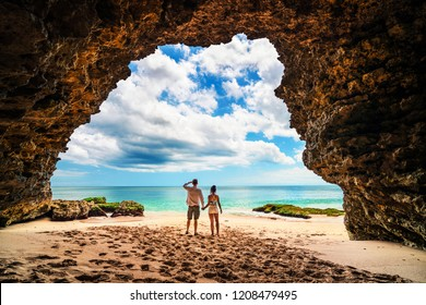 A loving couple enjoying the breathtaking views of the tropical sandy beach with green coconut palm trees and beautiful clean sea ocean on a background of blue sky