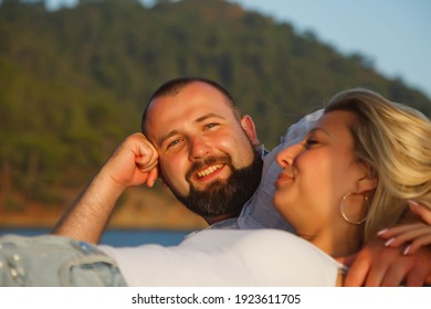 Loving couple enjoying honeymoon on beach hotel with luxury view walking shows emotion on sea background. Happy lovers on romantic trip fun on summer vacation evening. Concept romance and relaxation