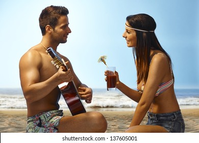 Loving couple enjoying sunset on the beach, man playing guitar, girl drinking cocktail.