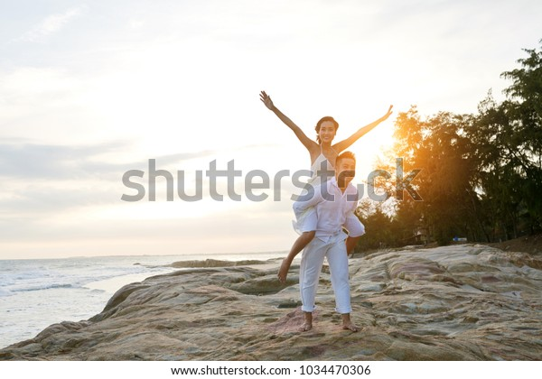 Loving couple enjoying vacation at exotic resort: joyful Asian man giving piggyback ride to his beautiful girlfriend with outstretched arms, picturesque seascape on background