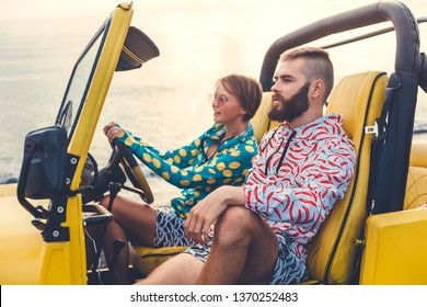 A loving couple in fashionable clothes travel around the paradise exotic islands in a yellow jeep on the beaches and off-road, the real active crazy travelers, a bearded guy and a cheap girl, USA,Bali