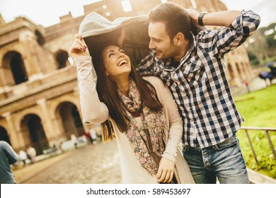 Loving couple in front of the Colosseum in Rome while raining