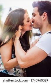 Liebende Paar Mädchen küsst und beißt die Lippe ihres Freundes. Intensive Liebe zwischen zwei jungen Menschen, die sich gegenseitig umarmen.